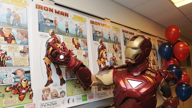 IMAGE DISTRIBUTED FOR PHONAK - Marvel's Iron Man helps unveil a poster developed in partnership between Phonak and Marvel Custom Solutions that is designed to promote hearing health in children and help remove the stigma associated with children wearing hearing aids, Tuesday, Feb. 26, 2013, in New York.  (Photo by Diane Bondareff/Invision for Phonak)