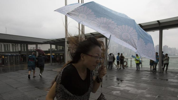 A woman braves gusty wind outside a shopping mall during Typhoon Usagi in Hong Kong