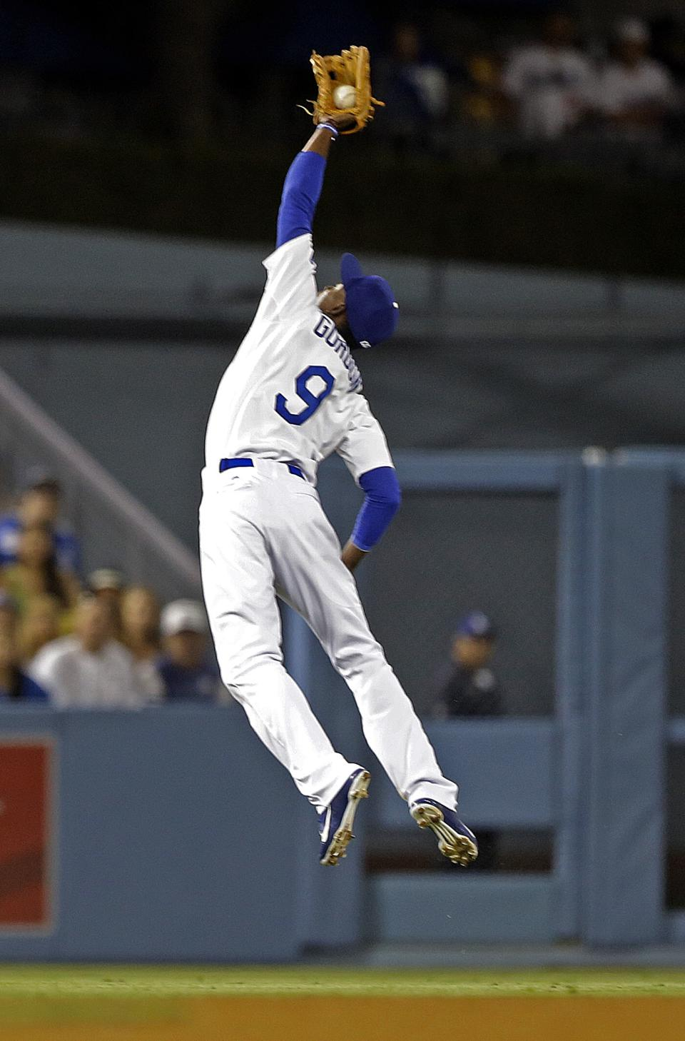 Los Angeles Dodgers shortstop Dee Gordon leaps for a high fly off Washington Nationals' Denard Span in the eighth inning of a baseball game in Los Angeles Tuesday, May 14, 2013. (AP Photo/Reed Saxon)
