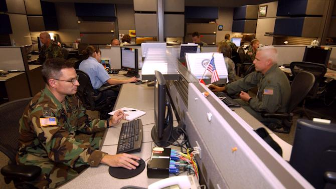 FILE - This Aug. 25, 2004 file photo shows unidentified analysts at the Combined Intelligence and Fusion Center for NORAD/Northcom in Colorado Springs, Colo. A multibillion-dollar information-sharing program that was created in the aftermath of 9/11 has improperly collected information about innocent Americans and produced no valuable intelligence on terrorism, according to a Senate report that describes an effort that ballooned far beyond anyone's ability to control. (AP Photo/David Zalubowski/File)