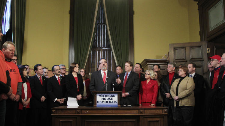 Members of the Michigan House Democrats and supporters stand in the office of House Democratic Leader Rick Hammel, center, in Lansing, Mich., Monday, Dec. 10, 2012, to denounce the state's right-to-work legislation which was passed last week in Lansing. (AP Photo/Carlos Osorio)