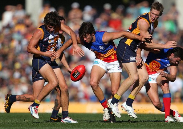 Rohan Bewick of the Lions contests for the ball against Andrew Gaff and Scott Selwood of the Eagles during the round 18 AFL match between the West Coast Eagles and the Brisbane Lions at Patersons Stad