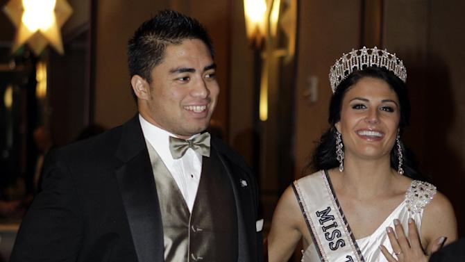 Notre Dame linebacker Manti Te'o is escorted by Miss Texas Ali Nugent as he carries the Lombardi Award to an interview room after a ceremony, Wednesday, Dec. 5, 2012, in Houston. Te'o, also a Heisman Trophy finalist, had 103 tackles and seven interceptions this year to help the undefeated Fighting Irish reach the BCS championship game against Alabama. (AP Photo/Houston Chronicle, Melissa Phillip)