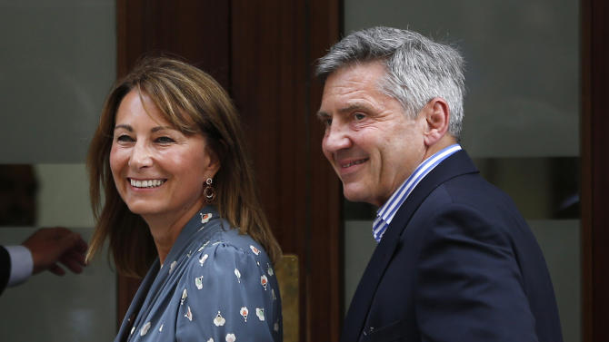 Carole and Michael Middleton, the parents of Kate, Duchess of Cambridge, smile as they arrive at St. Mary's Hospital exclusive Lindo Wing in London, Tuesday, July 23, 2013, where the Duchess gave birth on Monday July 22. The Royal couple are expected to head to London's Kensington Palace from the hospital with their newly born son, the third in line to the British throne. (AP Photo/Lefteris Pitarakis)