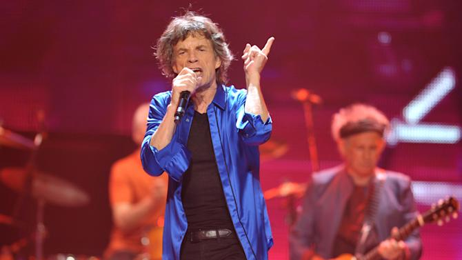 "FILE - This May 18, 2013 file photo shows Mick Jagger, center, and Keith Richards, of the Rolling Stones performing on the ""50 & Counting"" tour at the Honda Center in Anaheim, Calif. Rolling Stones memorabilia will be displayed in a new exhibit, ""Rolling Stones 50 Years of Satisfaction,"" at the Rock and Roll Hall of Fame in Cleveland. The exhibit opens on Friday, May 24. (Photo by John Shearer/Invision/AP, file)"