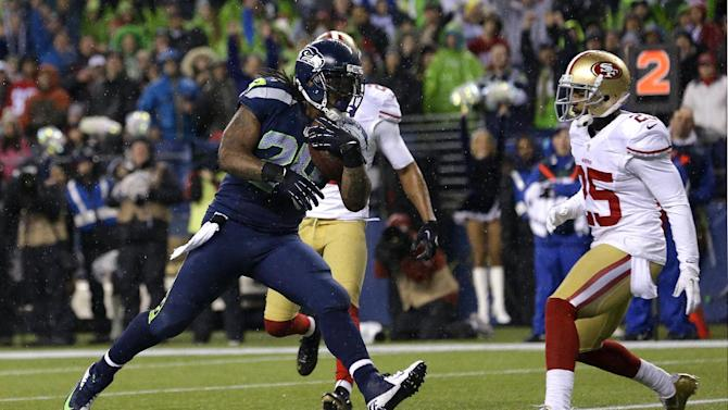 Seattle Seahawks' Marshawn Lynch scores his second touchdown of the game against the San Francisco 49ers in the first half of an NFL football game as San Francisco 49ers' Tarell Brown looks on at right, Sunday, Dec. 23, 2012, in Seattle. (AP Photo/Elaine Thompson)