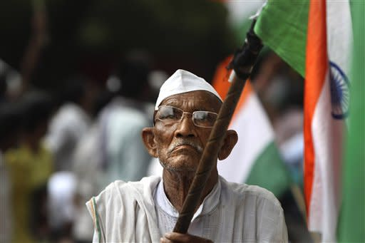 A supporter of India's anti-corruption activist Anna Hazare holds an Indian flag as he participates in a protest at Jantar Mantar, in New Delhi, India, Friday, July 27, 2012. Three supporters of Hazare entered the third day of their indefinite fast to pressure the government into passing a strong law against corruption. (AP Photo/Rajesh Kumar Singh)