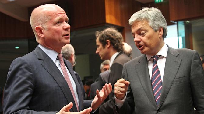 British Foreign Secretary William Hague, left, talks with Belgium's Foreign Minister Didier Reynders, during the EU foreign ministers meeting, at the European Council building in Brussels, Monday, May 27, 2013. The European Union nations remain divided on Monday whether to ease sanctions against Syria to allow for weapons shipments to rebels fighting the regime of Syria's President Bashar Assad. (AP Photo/Yves Logghe)