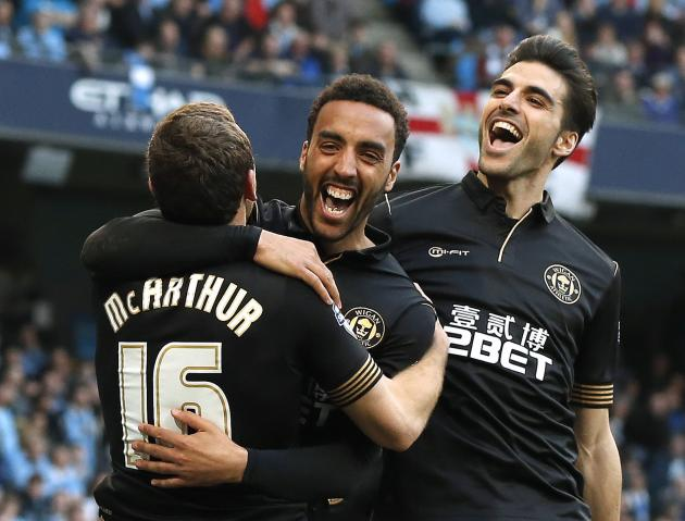 Wigan Athletic's Perch celebrates with teammates McArthur and Gomez after scoring a goal against Manchester City during their English FA Cup quarter final match in Manchester