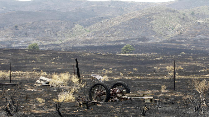 A piece of farm equipment sits in a burned field, after the High Park wildfire came through, near Bellvue, Colo., on Monday, June 18, 2012. The wildfire has burned over 180 homes.  (AP Photo/Ed Andrieski)