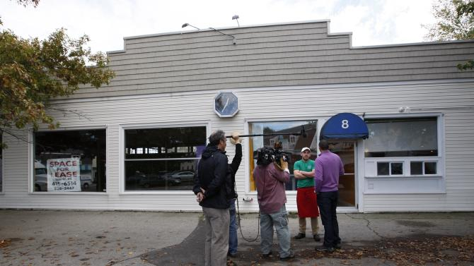 A pizzeria worker is interviewed by a TV crew in front of the former fitness studio where prostitution has been alledged to have occured in Kennebunk, Maine, Friday, Oct. 12, 2012. The police department's plan to release some of the more than 150 names of suspected clients was delayed Friday by last-minute legal wrangling. Alexis Wright, a 29-year-old fitness instructor from Wells, Maine, has pleaded not guilty to prostitution, invasion of privacy and other charges for allegedly accepting money for sex and secretly videotaping her encounters. Her business partner, Mark Strong Sr., a 57-year-old insurance agent and private investigator from Thomaston, Maine, pleaded not guilty to 59 misdemeanor charges.(AP Photo/Robert F. Bukaty)