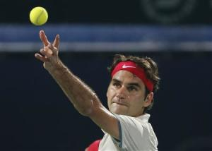 Federer of Switzerland serves to Rosol of the Czech Republic during their men's singles match at the ATP Dubai Tennis Championships
