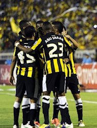 Al-Ittihad club players celebrate after scoring a goal during an AFC Champions League match in May. The classic east-west match between Al Ittihad and Guangzhou Evergrande pits the competition's only double champions against the rich newcomers from China