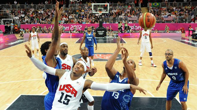 U.S. forward Carmelo Anthony, second from left, reacts after shooting while being challenged by French forward Boris Diaw, right, next to French guard Tony Parker, right, during the men's basketball preliminary round group A match between the United States and France at the 2012 Summer Olympics, on Sunday, July 29, 2012 in London.  (AP Photo/Mark Ralston, Pool)