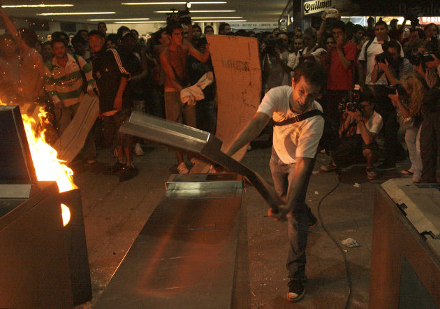 A demonstrator destroys turnstiles during riots at Once railway station in Buenos Aires, Argentina, Friday, Feb. 24, 2012. The discovery of a 51st victim Friday two days after Argentina&#39;s deadliest train wreck in decades left the man&#39;s family devastated and prompted rock-throwing and other violence by protesters holding vigil at the scene. Riot police responded with tear gas and batons, clearing the station and making arrests. (AP Photo/Alberto Raggio, DyN)