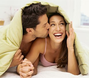 couple happy in bed cuddling having fun