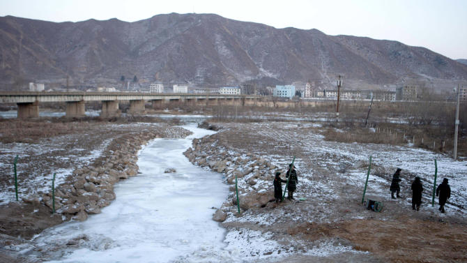 In this Saturday, Dec. 8, 2012 photo, Chinese paramilitary policemen build a fence across from North Korea, seen in the background from the Chinese border town of Tumen in eastern China's Jilin province. Over the past year, Kim Jong Un has intensified a border crackdown that has attempted to seal the once-porous 1,420-kilometer (880-mile) frontier with China, smugglers and analysts say, trying to hold back the onslaught.(AP Photo/Ng Han Guan)