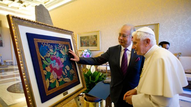 In this image made available by the Vatican newspaper Osservatore Romano, Pope Benedict XVI receives a present from Malaysia Prime Minister Najib Razak, left, in the pontiff's summer residence in Castelgandolfo in the Alban Hills south of Rome, Monday, July 18, 2011. After the meeting, the Vatican and the mostly Muslim Asian nation of Malaysia established diplomatic relations. Malaysia was one of fewer than 20 countries in the world lacking formal diplomatic ties with the Vatican. Roman Catholics and other Christians compromise nearly 10 percent of Malaysia's 28 million people.  (AP Photo/Osservatore Romano, HO) EDITORIAL USE ONLY