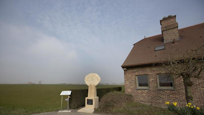 In this photo taken on March 18, 2015, a stone marker to show visitors the site of World War I battlefield, Kitcheners Wood, is placed next to a residential house near Ypres, Belgium. Private James Duffy, soldier and 1914 Boston Marathon winner, was among those injured during a midnight assault an April 22, 1915 on German positions at Kitchener's Wood after the first gas attacks. Duffy later died of his wounds at a nearby field hospital. (AP Photo/Virginia Mayo)