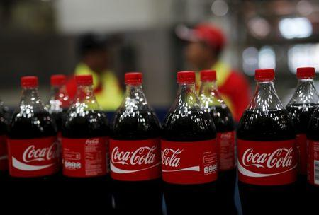 Workers stand near bottles of Coca-Cola on a newly inaugurated production line at the Cikedokan Plant in Bekasi, West Java near Jakarta