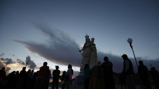 """Pilgrims stand at the base of the statue of the Virgin Mary on Santa Barbara hill as the sun begins to rise in the mining city of Oruro, Bolivia, Friday, Feb. 1, 2013. The statue, known in Spanish as """"Virgen del Socavón,"""" or the Virgin of the Tunnel, is Oruro's patron, venerated in particular by miners and folkloric Carnival dancers. The statue was unveiled on Friday to mark the start of Carnival in Oruro, which coincides with celebrations honoring the Virgin that starts on Saturday, Bolivia's largest religious event. (AP Photo/Juan Karita)"""