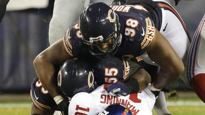 New York Giants quarterback Eli Manning (10) gets sacked by Chicago Bears linebacker Lance Briggs (55) and defensive end Corey Wootton (98) in the second half of an NFL football game, Thursday, Oct. 10, 2013, in Chicago. (AP Photo/Nam Y. Huh)