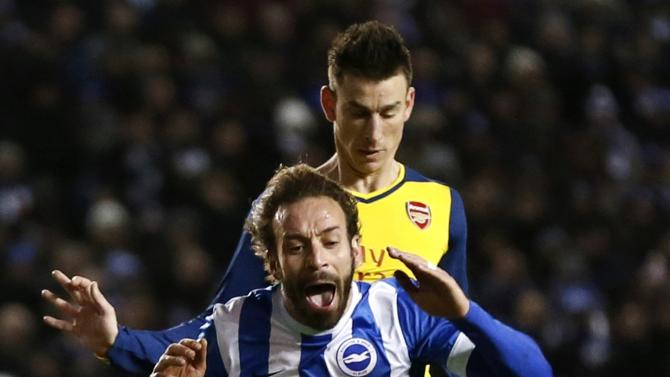 Brighton and Hove Albion's Calderon is challenged by Arsenal's Koscielny during their FA Cup fourth round soccer match in Brighton