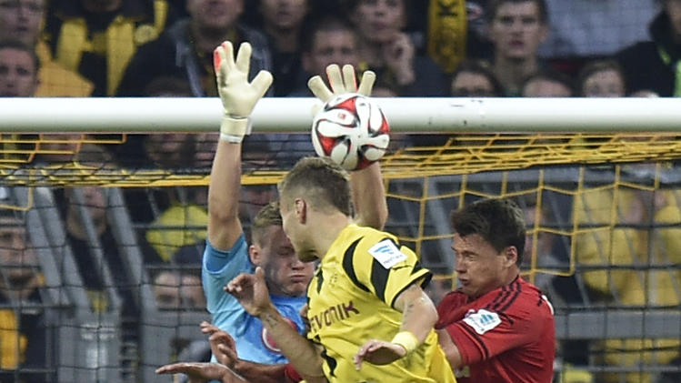 Leverkusen's goalkeeper Bernd Leno saves a ball in front of Dortmund's Ciro Immobile from Italy during the German Bundesliga soccer match between Borussia Dortmund and Bayer Leverkusen in Dortmund, Germany, Saturday, Aug. 23, 2014, 2014. (AP Photo/Martin Meissner)