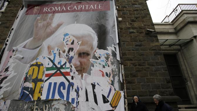 FILE - This March 1, 2013 file photo shows nuns walking behind a billboard with a torn poster of Pope Benedict XVI in Rome. These are crazy days in Rome - where limbo reigns in parliament and papacy. Italy is usually a pretty anarchic place, with people bucking rules on everything from crossing the street to paying taxes. But the anarchy's going a bit far: Who's running the country? Who's running the church? Nobody really knows. (AP Photo/Gregorio Borgia, files)