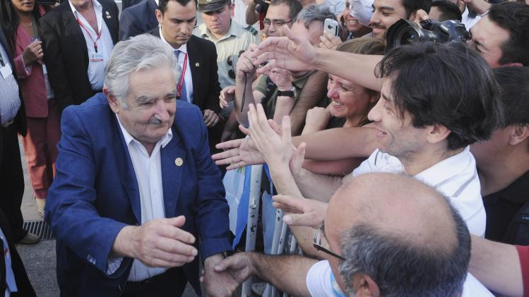 Mujica greets people after a meeting with Pinera in Santiago