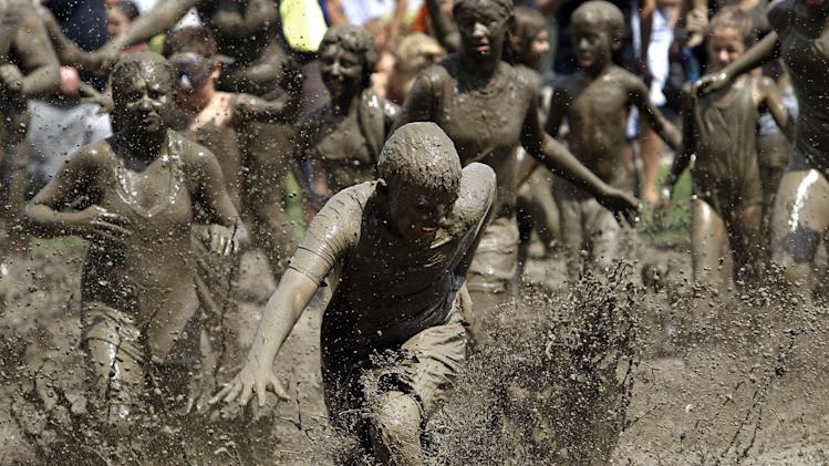 Logan Palshan, 12, of Taylor runs in the mud in Westland, Mich., Tuesday, July 9, 2013. Hundreds of kids enjoyed the annual Mud Day event in a 7-by-150-foot mud pit. (AP Photo/Paul Sancya)