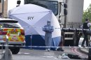 A tent is erected near the scene of an attack in Woolwich southeast London Wednesday, May, 22, 2013. A British official says a violent attack near a London barracks is being investigated as a possible terrorist act. Police said two men attacked another man on Wednesday. One man is dead and two others were injured. (AP Photo/Alastair Grant)