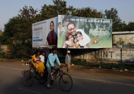 In this photo taken Wednesday, April 13, 2011, a family cycle past a government's advertisement board in support of baby girls in Morena in the Central Indian State of Madhya Pradesh. Despite a booming economy and big cities full of glittering malls and luxury cars, the country is failing its girls in India's most recent census. Early results show India has only 914 girls under age 6 for every 1,000 boys. The census in Morena showed that for every 1,000 boys only 825 girls in the district made it to their sixth birthdays, down from an already troubling 829 a decade ago.