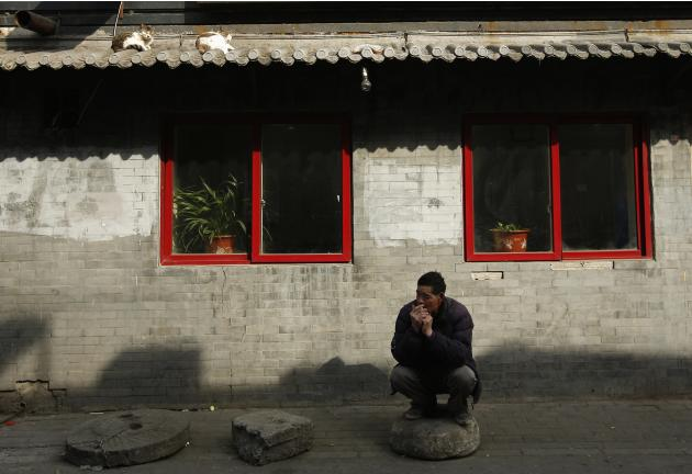 A man smokes a cigarette underneath a roof where cats are taking a nap, in Beijing