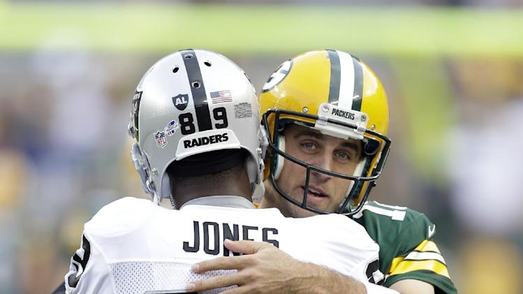 Green Bay Packers' Aaron Rodgers hugs Oakland Raiders' James Jones before an NFL preseason football game Friday, Aug. 22, 2014, in Green Bay, Wis. Jones played for the Packers before the Raiders