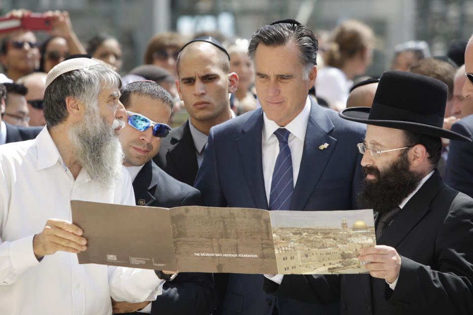 Republican presidential candidate and former Massachusetts Gov. Mitt Romney is presented with a booklet as he visits the Western Wall, in Jerusalem, Sunday, July 29, 2012. (AP Photo/Dan Balilty)