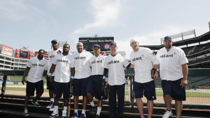 Dallas Cowboys head coach Jason Garrett, third from right, poses for a photo with several of the teams players before the start of the Home Run Derby Competition hosted by Reliant to benefit The Salvation Army on Wednesday, May 8, 2013 in Arlington, Texas. A total of $43,000 was raised for the charity. (Brandon Wade/AP Images for Reliant)