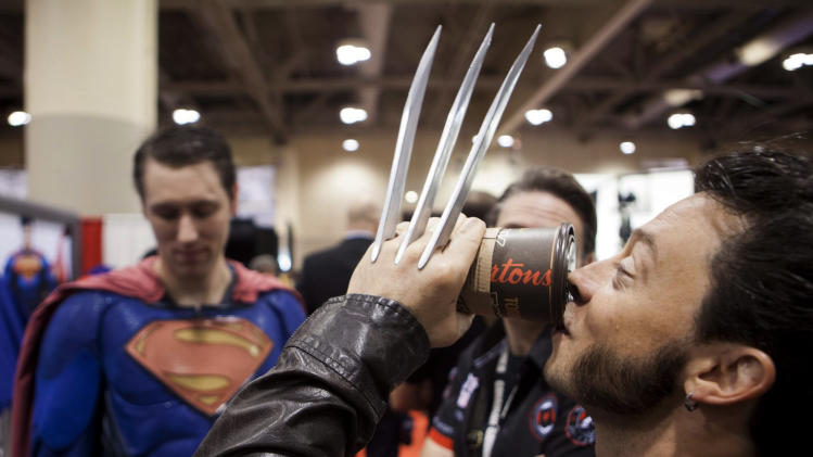 Ken Rice, dressed as in costume, drinks a coffee with friends at the FAN Expo Canada in Toronto, Friday, Aug. 29, 2014. (AP Photo/The Canadian Press, Jesse Johnston)