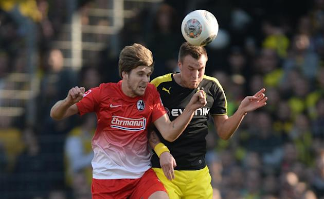 CORRECTS IDENTITY OF FREIBURG'S PLAYER AT LEFT TO PHILIPP ZULECHNER - Freiburg's Philipp Zulechner,  left, challenges for the ball with Dortmund's Kevin Grokreutz during the German first d