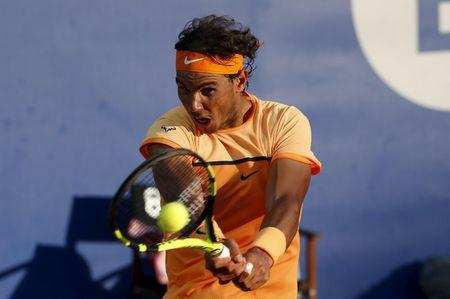Rafael Nadal of Spain returns a ball to Kei Nishikori of Japan during Barcelona Open tennis tournament in Barcelona