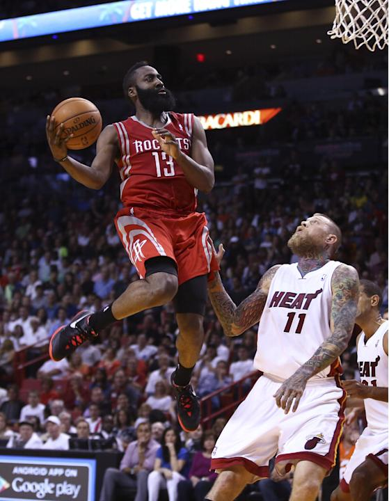 Houston Rockets' James Harden (13) goes over Miami Heat's Chris Andersen (11) for two points during the second half of an NBA  basketball game in Miami, Sunday, March 16, 2014. The Heat won 11
