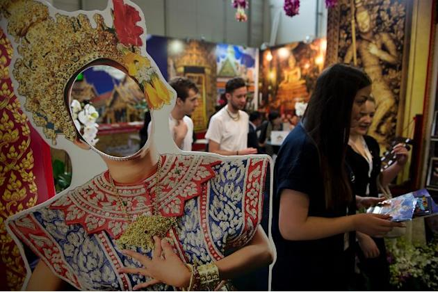Fair-goers walk past a cardboard cut-out featuring a traditional Thai dancer at the Bangkok stand of the ITB International Travel Trade Fair in Berlin on March 5, 2014
