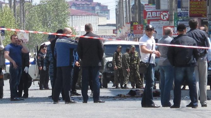 Police and forensic experts examine the site of an explosion in downtown Makhachkala, Dagestan on Wednesday, May 1, 2013. Russian police say a bomb  exploded in a busy shopping area in the capital of the restive republic of Dagestan, killing at least two people.  Dagestan is plagued by Islamic insurgents who frequently mount small attacks on police. (AP Photo/ NewsTeam/ Suleyman Aliev)