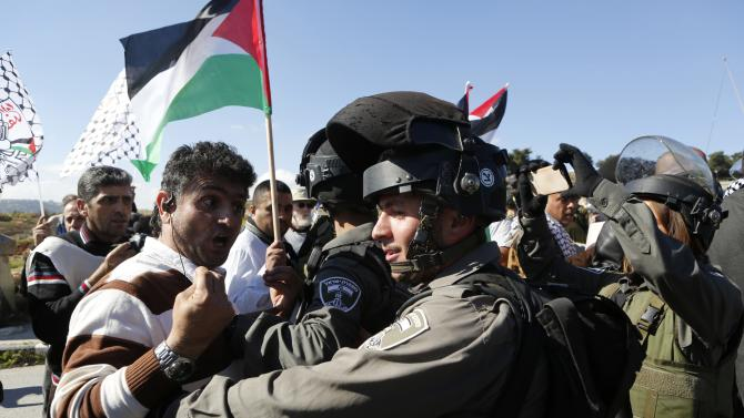 Palestinian protester argues with Israeli border policemen during a protest against Israeli settlements in Beit Fajjar town south of the West Bank city of Bethlehem