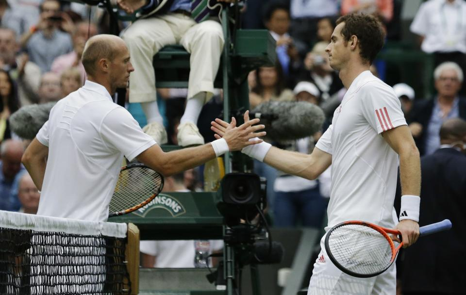 Andy Murray of Britain, right, is congratulated by Nikolay Davydenko of Russia following their first round men's singles match at the All England Lawn Tennis Championships at Wimbledon, England, Tuesday, June 26, 2012. (AP Photo/Anja Niedringhaus)