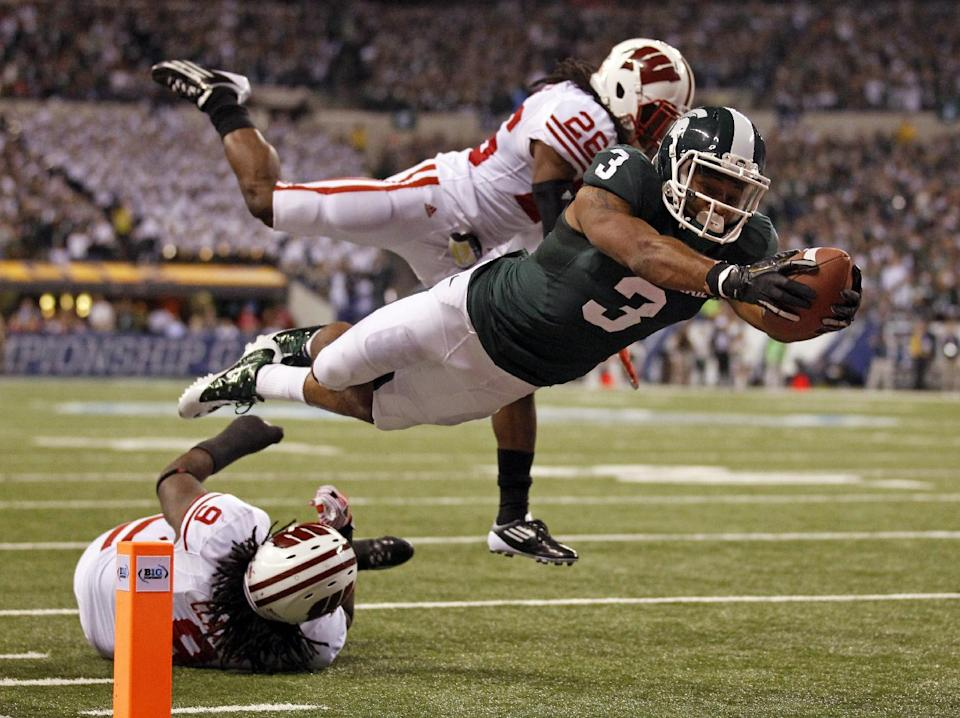 Michigan State's B.J. Cunningham (3) dives into the end zone for a touchdown in front of Wisconsin's Antonio Fenelus during the first half of the Big Ten conference championship NCAA college football game on Saturday, Dec. 3, 2011, in Indianapolis. (AP Photo/Michael Conroy)
