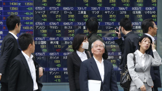 Passers-by watch an electronic stock board of a securities firm in Tokyo, Thursday, May 30, 2013. Japan's Nikkei 225 index closed down 737.43 points, or 5.15 percent, at 13,589.03 on Thursday as concerns that the Federal Reserve might start scaling back its stimulus program due to improvement in the U.S. economy sent Asian stock markets lower. (AP Photo/Koji Sasahara)