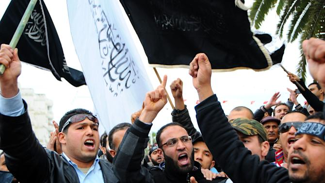 FILE - This Friday, Jan. 11, 2013 file photo shows Tunisian Islamists holding banners as they demonstrate in Tunis, Tunisia. Two years after the revolution that overthrew a dictator and started the Arab Spring, Tunisia is struggling with high unemployment and rising violence in its politics. After sounding the alarm for months over the rise of religious extremists, the opposition now warns that the new threat to this North African country's democratic transition are vigilante bands allied to the elected government. (AP Photo/Hassene Dridi, File)