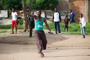 A protestor gestures towards police and Imbonerakure, …