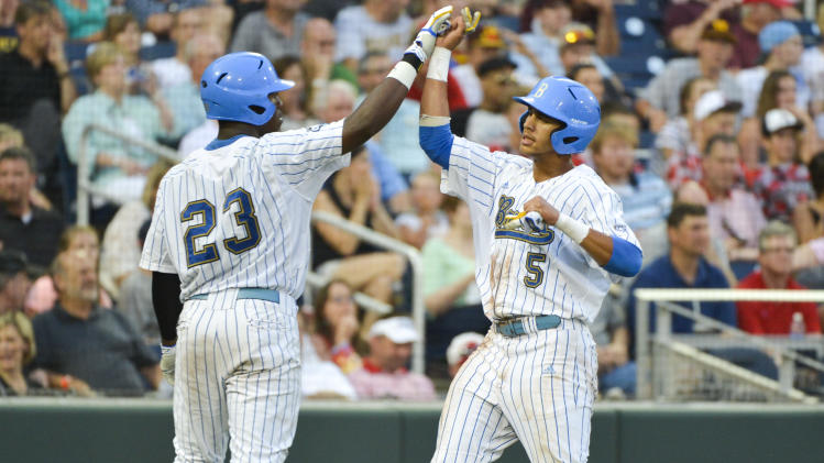 UCLA's Kevin Williams (5) is greeted by Brenton Allen (23) after he scored against Mississippi State on a single by Cody Regis in the fourth inning of Game 2 in their NCAA College World Series baseball finals, Tuesday, June 25, 2013, in Omaha, Neb. (AP Photo/Ted Kirk)